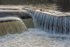 Flowing water cascading over a weir on yorkshire river Royalty Free Stock Images