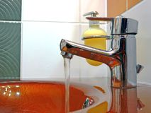 Flowing water faucet. Tap and sink in a modern bathroom Stock Photos