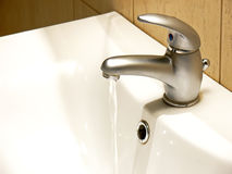 Flowing water faucet. Closeup of water flowing into a white porcelain sink from a chrome faucet Royalty Free Stock Image