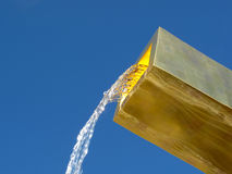Flowing water from golden fountain Stock Photography