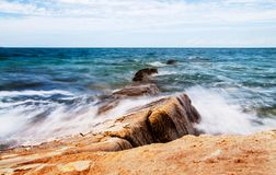 Flowing water over rocks on the beach Royalty Free Stock Photography