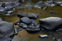 Flowing water over rocks and boulders Stock Photography