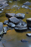Flowing water over rocks and boulders Royalty Free Stock Images