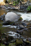 Flowing water over rocks and boulders Stock Photos