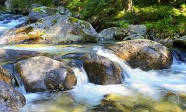 Flowing water over rocks in the stream. Stock Photography