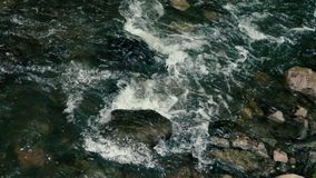 Slow motion footage. Flowing water over stones in mountines river stock video