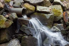 Flowing water from a pipe down to mossy rocks royalty free stock photos