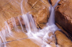 Flowing water on red rocks Royalty Free Stock Image