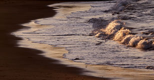 Flowing water reflections shining at sunset. Magnificent golden beach with flowing ocean reflections at sunset royalty free stock photography
