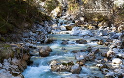 Flowing water with stone bridge Stock Photos