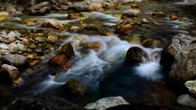 Flowing water stream through rocks royalty free stock photography