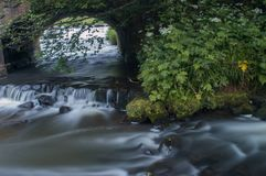 Flowing water turned milky white by a long exposure as it flows around green and brown mossy rocks. royalty free stock image