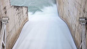 Flowing water through the water gate of the dam royalty free stock photography