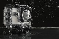 Flowing water on the waterproof action camera on wet black stone background stock photography