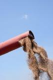 Flowing Wheat Grains. Combine harvester unloads wheat grains against blue sky Stock Images