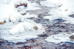 Flowing winter water with some ice. Water and ice, winter background Royalty Free Stock Photos