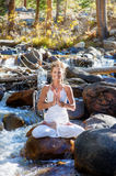 Flowing Yoga Woman. Woman in yoga lotus pose with lotus hand mudra while outdoors in a forest river royalty free stock photo