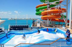 Flowrider Surf Simulator and Waterslides on sports deck, Royal Caribbean. Flowrider Surf Simulator onboard Liberty of the Seas cruise ship, Royal Caribbean royalty free stock photography