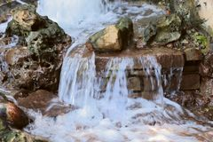 Flows of water flowing down the stones. Stormy flows of water. royalty free stock photography