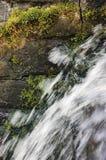 A fluência da cachoeira da cascata da água corrente espirra, granito decorativo obstrói o fundo, musgo verde, parede de pedra da  Imagens de Stock Royalty Free