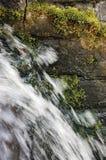 A fluência da cachoeira da cascata da água corrente espirra, granito decorativo obstrói o fundo, musgo verde, parede de pedra da  Imagem de Stock