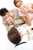 Flu. Doctor and young couple having the flu. Isolated over white background Stock Photos
