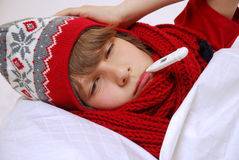 Flu. Boy in warm clothes with thermometer lying in bed Stock Image
