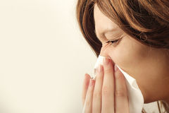 The flu. Young woman blowing her nose with handkerchief Royalty Free Stock Image