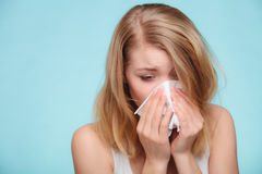 Flu allergy. Sick girl sneezing in tissue. Health. Flu cold or allergy symptom. Sick woman girl sneezing in tissue on blue. Health care Royalty Free Stock Photos