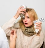 Flu and cold treatment. Girl in scarf examined by doctor. Fever and flu remedies. Woman consult with doctor. Doctor. Communicate with patient recommend stock photography