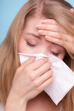 Flu fever. Sick girl sneezing in tissue. Health. Flu cold or allergy symptom. Closeup of sick young woman girl with fever sneezing in tissue on blue. Health care Royalty Free Stock Images
