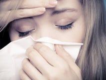 Flu fever. Sick girl sneezing in tissue. Health. Flu cold or allergy symptom. Closeup of sick young woman girl with fever sneezing in tissue. Health care. Studio Stock Images