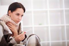 flu Giovane donna con freddo/influenza che si trova sul letto Immagini Stock
