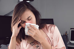 Flu and Headache. Asian woman in satin nightwear feeling unwell and sneeze on desk at home. People Caught Cold and flu Royalty Free Stock Image