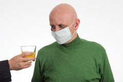 Flu illness young man in medicine healthcare mask looking at juice Royalty Free Stock Images