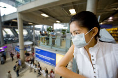 With flu mask at the airport. Asian woman at the international airport in bangkok Royalty Free Stock Image