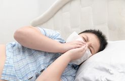 Flu. Obese boy got nose allergy. Flu sneezing nose sitting on bed, health care concept stock images