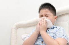 Flu. Obese boy got nose allergy. Flu sneezing nose sitting on bed, health care concept royalty free stock images