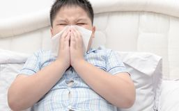 Flu. Obese boy got nose allergy. Flu sneezing nose sitting on bed, health care concept royalty free stock photo