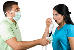 Flu and paranoia man. Couple with problems :woman is sick and want to sneeze in a white napkin and the man giving her a protective mask and making a scared face Stock Photo