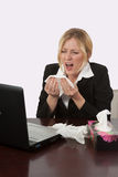 Flu Season. Blond caucasian woman wearing business attire sitting in front of laptop computer with a box of tissues blowing her nose royalty free stock images