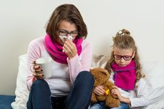 Flu season, sick mother and child at home. A women with a runny nose, she sneezes, using a handkerchief, drinking hot tea, medicine Stock Photo