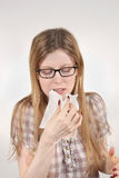 Flu season. Young woman sneezing into paper tissue during flu pandemic Royalty Free Stock Photography