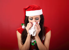 Flu. Unhappy frustration sick woman holding paper tissue near he. R nose and looking down in christmas night on red background Stock Images