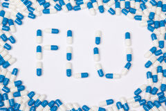 Flu word text made of blue tablets, pills and capsules Stock Images