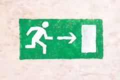 Fluchtwegzeichen über einem schwarzen Eingang Lizenzfreie Stockbilder