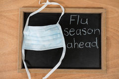 Flue season ahead written on chalk board with medical mask royalty free stock photo