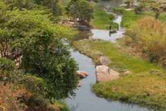 Fluent river with rocks, vegetation, fisherman and boat in afric. A. Lubango. Angola Stock Photo