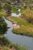 Fluent river with rocks, vegetation, fisherman and boat in afric Royalty Free Stock Photography