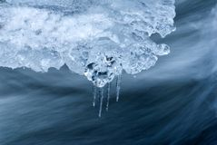 Fluent water. And icicles in mountain river Royalty Free Stock Photos